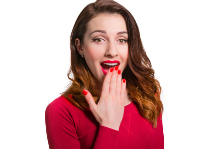 Pretty woman in red looking away in awe surprised with mouth open wide isolated on white background