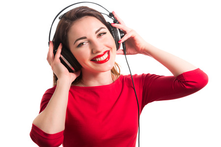 Girl in long-sleeve t-shirt wearing red lipstick touching big headphones listening to music smiling and looking at camera isolated on white background