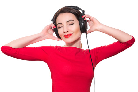 Attractive young adult woman in red clothes listening to the music touching big headphones with closed eyes isolated on white background