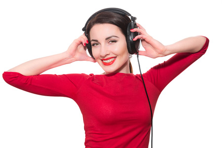 Wonderful teenager girl  listening to the music in big headphones in red clothes islolated on white background Imagens