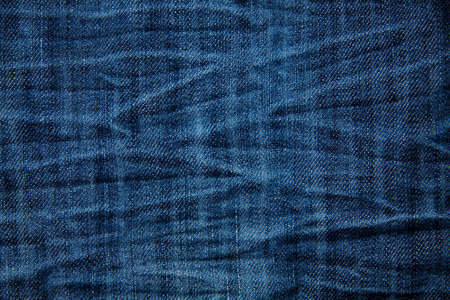 Blue wrinkled denim jeans texture, background Stock Photo