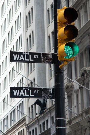 NEW YORK - JUNE 20: A symbolic photo of Wall street signs with a green traffic light on June 20, 2011 in New York. The green light is a symbol of prosperity.