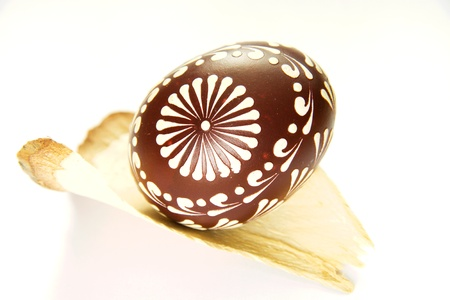 Painted easter egg on a slice of wood isolated on white Stock Photo