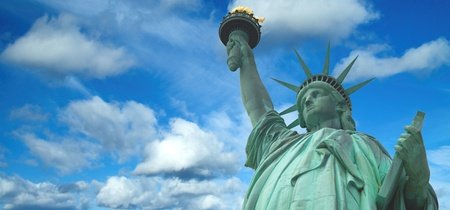 Statue of Liberty panorama with bright blue cloudy sky, New York Stock Photo