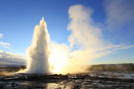 Strokkur Geysir Eruption against the Sun, Iceland Stock Photo