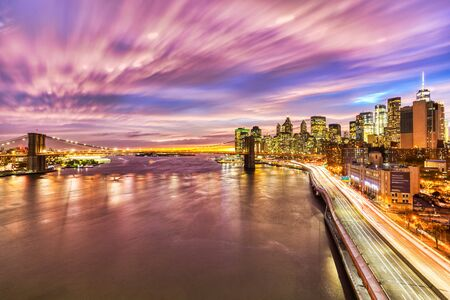 View of Lower Manhattan with Brooklyn Bridge at sunset, New York City, USA