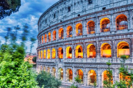 Illuminated Colosseum at Dusk, Rome, Italy      Keywords: rome, colosseum, monument, landmark, coliseum, italy, italian, sky, sunset, blue, ancient, architecture, roman, famous, europe, amphitheater, arena, stadium, historic, empire, gladiator, roma, sunrise, dusk, twilight, illuminated, impressive, panorama, landscape, arc, cloud, christian, centurion, shadow, emperor, arch, sun, province, grass, archeology, heritage, dawn, past, brick, summer, theater, travel, building, european Stock Photo