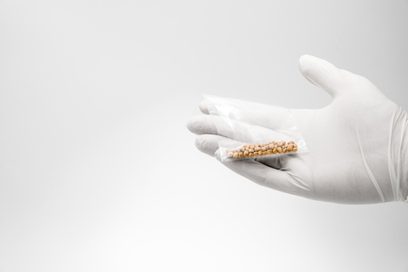 Man holding bag of gallstones while wearing examination gloves