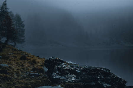 view on foggy lake mortirolo in mountain