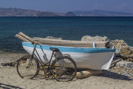 symbols  metaphors: Boat and bike on the background of the sea Stock Photo