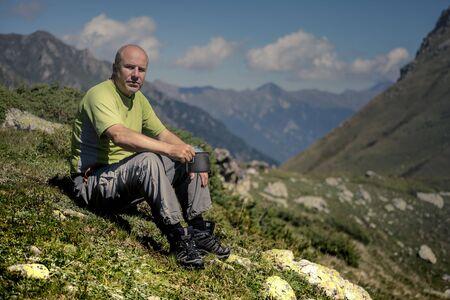 seated man: Hombre asentado con una taza en las manos sobre un fondo de montañas. Foto de archivo