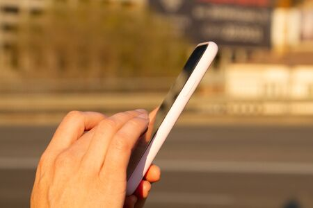 Close-up Shot of female hands using smartphone on city street near the road, searching or social networks or typing message
