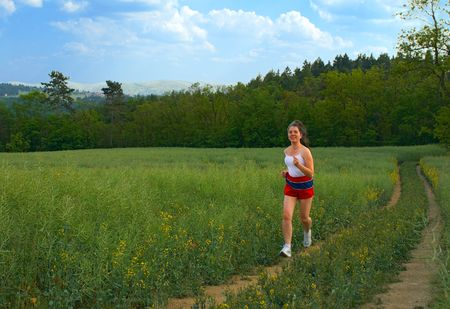 Day time training. The young woman runs on rural roads. photo