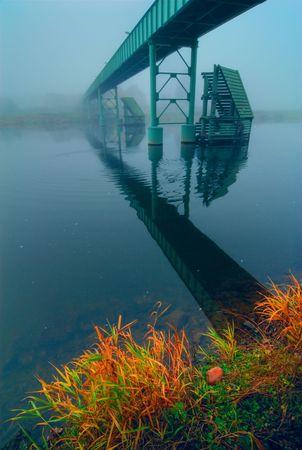 The bridge through the river. Foggy morning. photo
