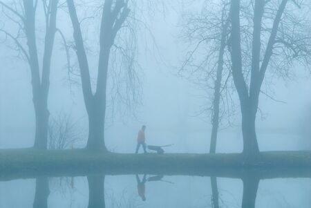 earlier: The gardener on coast of lake. Earlier morning. A fog