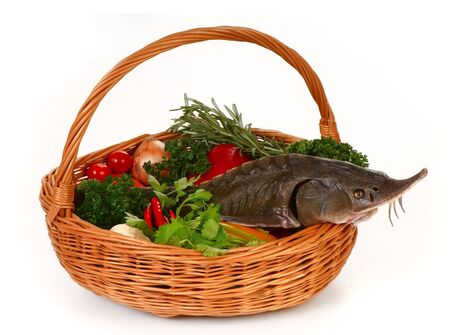 Still life. Basket with fresh vegetables and sturgeon.  photo