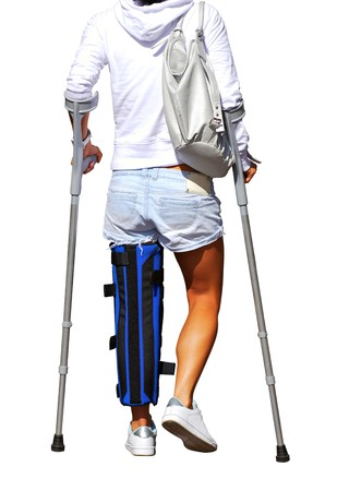 Girl with a broken leg and crutches (white background) photo