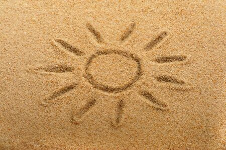 Childrens drawing of the sun on sand