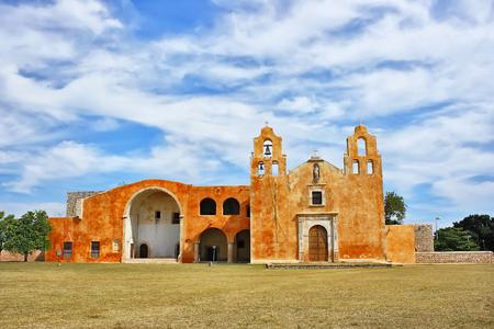san miguel arcangel: Una imagen panorámica del convento colonial de San Miguel Arcangel en Mani, Yucatán. México, luz del día, con un fondo de cielo azul y nubes, en el primero plano la hierba verde, color, horizontal
