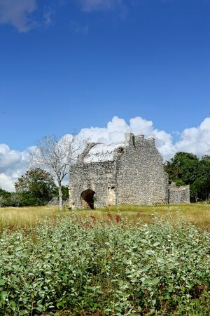 An image of the open chapel of Dzibilchaltun, Yucatan. Mexico, built in 1592 S. XVI, daylight, with a background of blue sky and clouds, in the foreground grass, color, vertical Stock Photo