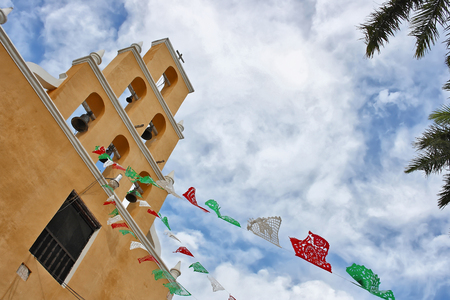 An image of the facade of a viceroyal church in Yucatan, decorated with festive plastic banners, celebrating the patron saint of the people, daylight, blue sky, horizontal