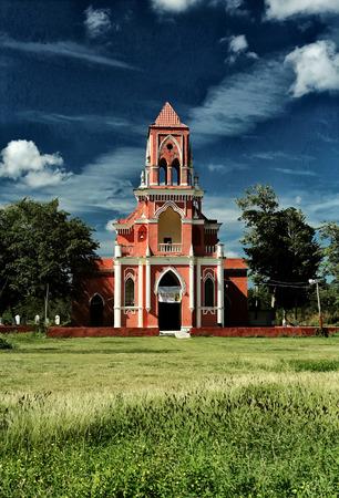 ignacio: An image of neo-Gothic church San Ignacio de Loyola in the town of San Ignacio. Progress. Yucatan. Vivid colors, green grass and background a blue sky with clouds, color, daylight