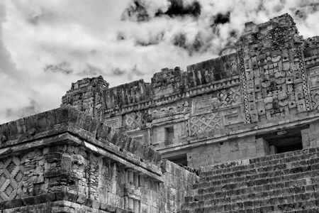 nuns: An image of a fragment of the square called The Quadrangle of the Nuns, with architectural details of Puuc style in the ancient city of Uxmal, Yucatan. Mexico; With a fountain of clouds and dark sky, black and white, daylight.