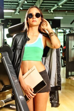 constant: A photograph of a beautiful mexican teenager who attends gyms to exercise, dressed in multicolored sportswear together with fashion accessories as a portfolio, leather jacket and wallet, with an attitude of safety and relaxation, color with a background o Stock Photo