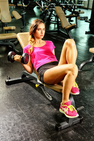 An image of a beautiful, Latin American teenage girl sitting on a multi-exercise seat, dressed in black shorts and a pink T-shirt and tennis, with her legs extended and on this device, holds a dumbbell in her hand to exercise her arm, looking toward The c Stock Photo