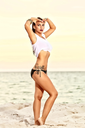 An image of a pretty Latina woman in a bikini and with a short T-shirt, showing a tattoo at the waist, is standing on the sand with both hands on her face, looking sideways. Stock fotó