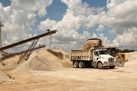 storage: An image of a quarry where you can see the transport bands of stone material already sprayed, being placed by a retro digger towards a truck to transport, color, daylight