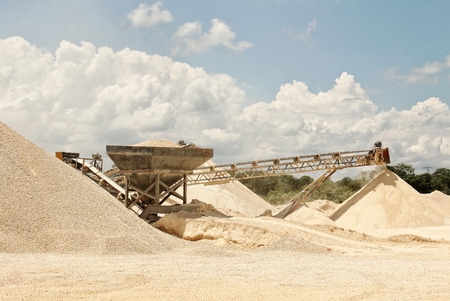 An image of a quarry where you can see the transport bands of stone material already crushing, in different grades of pulverized, which is being stacked for transfer, color, daylight