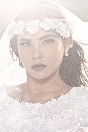 Designer Trouwjurk.Een Afbeelding Van Een Zeer Aantrekkelijke Mexicaanse Jonge Vrouw Gekleed In Een Designer Trouwjurk En Met Een Sluier Over Haar Gezicht Poseren Voor