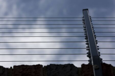 Electric fence on a brick wall photo
