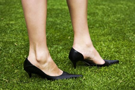 Close-up shot of a womans beautiful legs with black high heels on green grass. photo