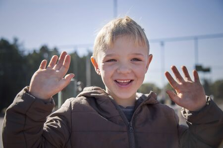 Closeup portrait of a happy beautiful young boy smiling happily. He is raising he's hand with open palms. He is wearing a dirty jacket.