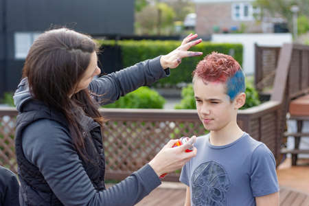 happy family having fun at home. the boy's mother is spraying he's hair with colored dye.