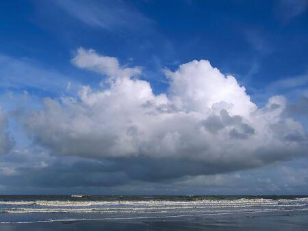 Huge beautiful cloud and windy sea. Blue sky. photo