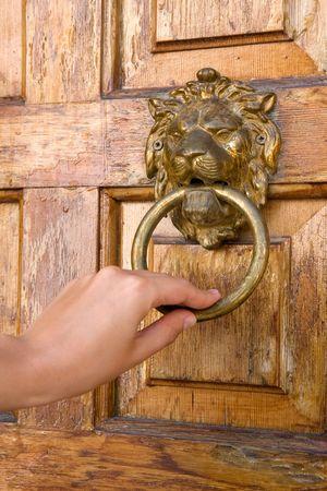 doorknocker: Lionhead door knocker with ladies hand. Wooden door.