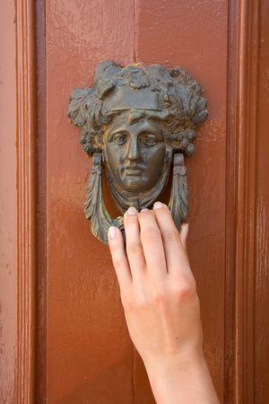 knocker: Old door knocker with ladies hand. Wooden door.