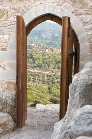 View through ancient wooden doorway of a sunny scene with valley and rocks.