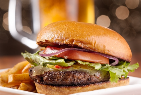 gourmet cheeseburger with mug of beer in background Stock Photo - 9833771