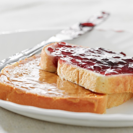 peanut butter and jelly: Peanut butter and jelly on pieces of bread.