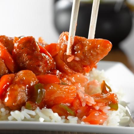 zoet en zuur varkensvlees op rijst dat Eaton met stokjes Stockfoto