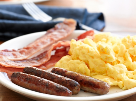 cooked meat: breakfast meal with sausage and scrambled eggs with bacon.