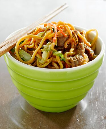 beef lo mein in a bowl with chopsticks photo