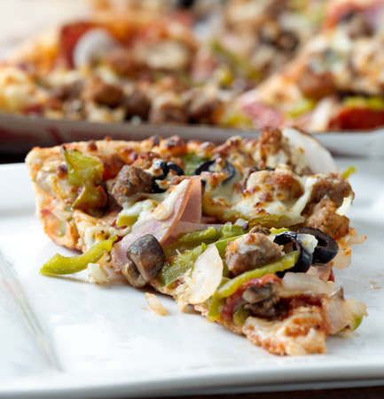 slice of pizza with supreme toppings on a plate photo