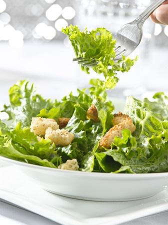 het eten van een lommerrijke groene salade met vork Stockfoto