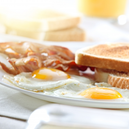 sunny side up: bacon, eggs and toast breakfast and rays of sunlight