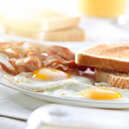 huevos fritos: tocino, huevos y tostadas del desayuno y los rayos de la luz del sol